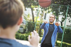 Two males playing basketball