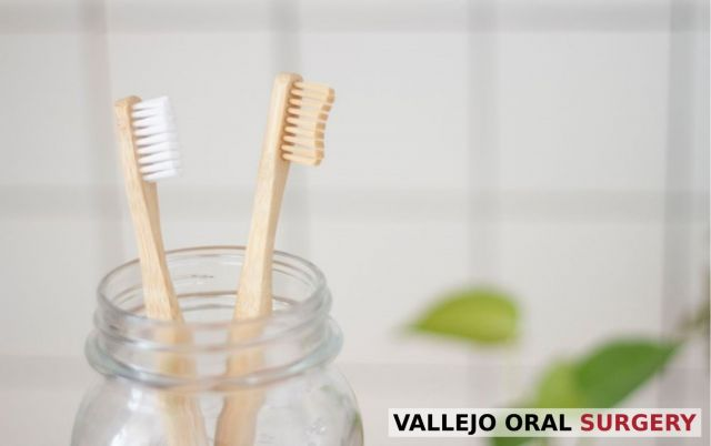 Two recently changed wood toothbrushes inside a clear glass jar - Vallejo, CA